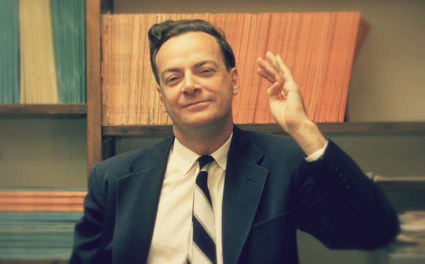1959: American physicist Richard Feynman (1918 - 1988) stands and raises one hand, in front of some shelves at Cal Tech University, Sacramento, California. (Photo by Joe Munroe/Hulton Archive/Getty Images)